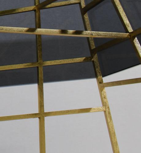 Kenzo Modern Center Table with a smoked glass top, this piece's polished brass structure and abstract geometric base